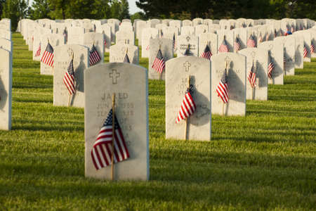 Endless row of white marble gravestones continues above hilltop at the Fort Logan National Cemetery in Denver, Colorado. American flags decorating each grave to mark the Memorial Day. Publikacyjne