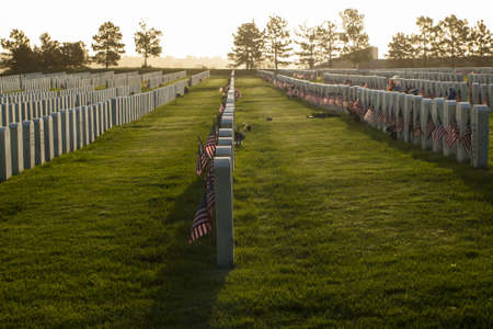 fort logan colorado: Endless row of white marble gravestones continues above hilltop at the Fort Logan National Cemetery in Denver, Colorado. American flags decorating each grave to mark the Memorial Day. Stock Photo