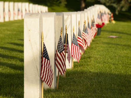 fort logan national cemetery: Endless row of white marble gravestones continues above hilltop at the Fort Logan National Cemetery in Denver, Colorado. American flags decorating each grave to mark the Memorial Day. Stock Photo