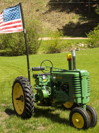 Old farm tractor with American flags.