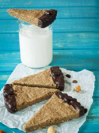 Gourmet hazelnut and coffee chocolate bars on white parchment paper. photo