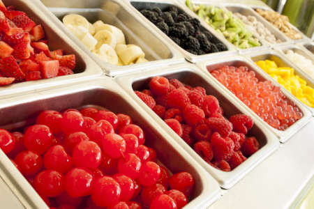 frozen fruit: Frozen yogurt toppings bar. Yogurt toppings ranging from fresh fruits, nuts, fresh-cut candies, syrups and sprinkles. Stock Photo
