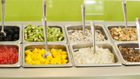 Frozen yogurt toppings bar. Yogurt toppings ranging from fresh fruits, nuts, fresh-cut candies, syrups and sprinkles. Imagens