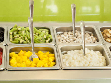 ranging: Frozen yogurt toppings bar. Yogurt toppings ranging from fresh fruits, nuts, fresh-cut candies, syrups and sprinkles. Stock Photo