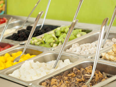 Frozen yogurt toppings bar. Yogurt toppings ranging from fresh fruits, nuts, fresh-cut candies, syrups and sprinkles. Stock fotó