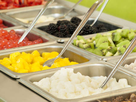 Frozen yogurt toppings bar. Yogurt toppings ranging from fresh fruits, nuts, fresh-cut candies, syrups and sprinkles. Stock Photo