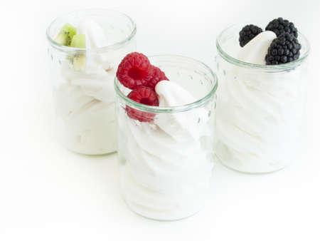 caneberries: Frozen soft-serve yogurt in cup on white background.