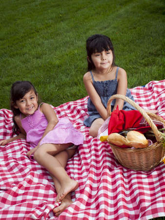 11 year old girl: Young family having picnic at the park.