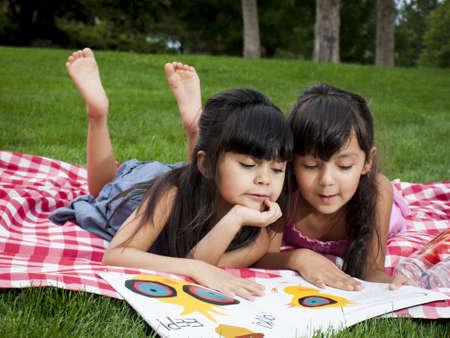Dos hermanas libro de lectura en el parque. Foto de archivo - 14693525