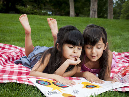Two sisters reading book in the park. Stockfoto