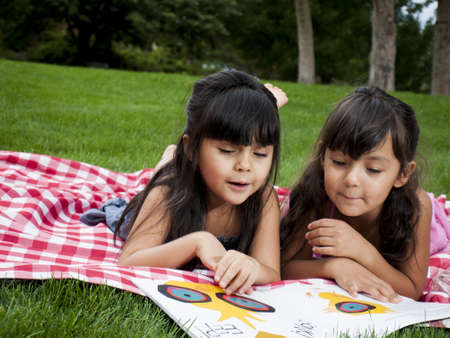 Two sisters reading book in the park. photo