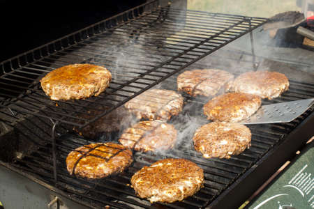 Gourmet hamburger parries on the grill. Imagens