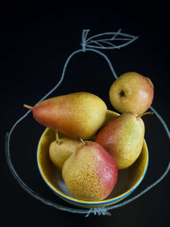 antiquity: Ripe pear on black background. The cultivation of the pear in cool temperate climates extends to the remotest antiquity, and there is evidence of its use as a food since prehistoric times. Stock Photo