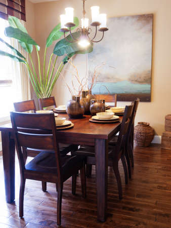 Modern dining room with table set for family dinner. Редакционное