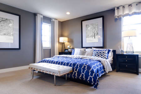 contemporary: Modern master bedroom with blue wall and white linens.