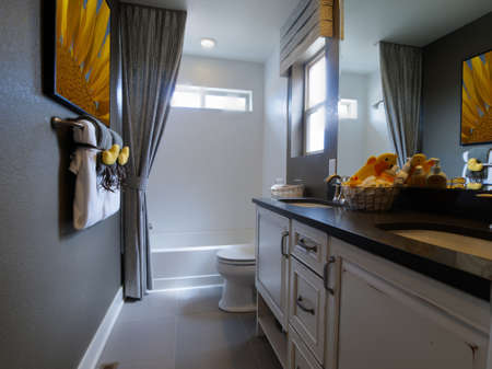 Kids badkamer met gele eenden decor en witte kasten.
