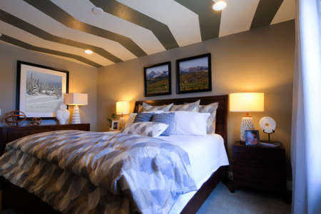 Modern master bedroom with large pictures and custom painted ceiling.