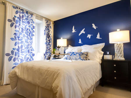 nightstand: Modern master bedroom with blue wall and white linens.