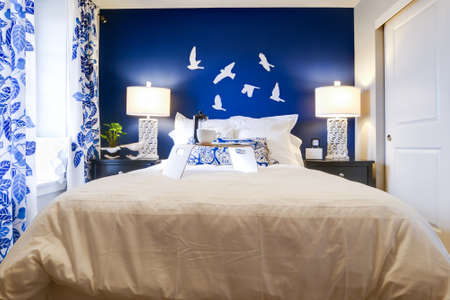 Modern master bedroom with blue wall and white linens. Stock Photo - 15079369