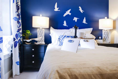 Modern master bedroom with blue wall and white linens. Stock Photo - 15079373