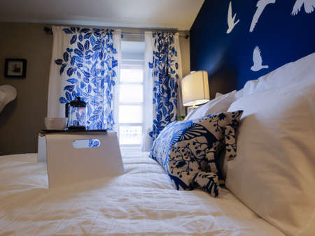 Modern master bedroom with blue wall and white linens.