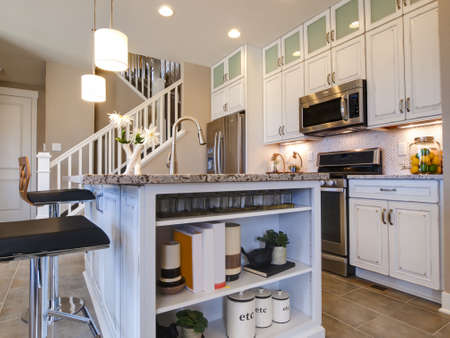 appliances: Modern kitchen with white cabinets and stainless appliances.