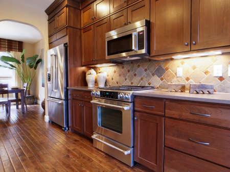 木製のキャビネットとステンレス電化製品とモダンなキッチン。
