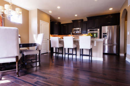 luxurious: Modern kitchen with dark wood cabinets and hardwood floors.