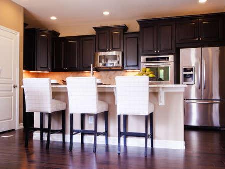 Moderne keuken met donkere houten kasten en hardhouten vloeren. Redactioneel