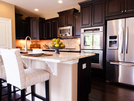Modern kitchen with dark wood cabinets and hardwood floors. Imagens - 15079365