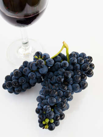 Grapes and red wine in glass on white backgound. 写真素材