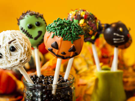 vegetare: Halloween gourmet cake pops with holiday decor on orange backround. Stock Photo