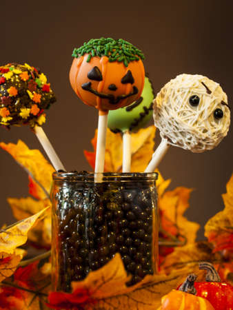 Halloween gourmet cake pops with holiday decor on brown backround. photo