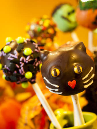 vegetabilis: Halloween gourmet cake pops with holiday decor on orange backround. Stock Photo