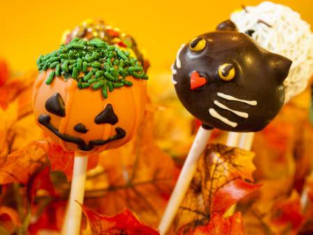 Halloween gourmet cake pops with holiday decor on orange backround. Stock Photo