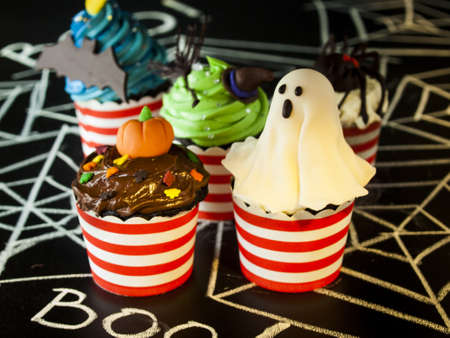 webb: Halloween gourmet cupcakes with holiday decor black background.