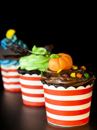 vegetabilis: Halloween gourmet cupcakes with holiday decor black background.