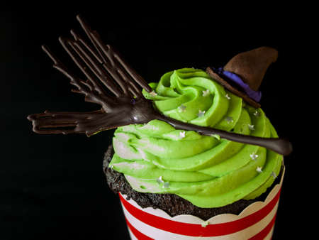Halloween gourmet cupcakes with holiday decor black background.