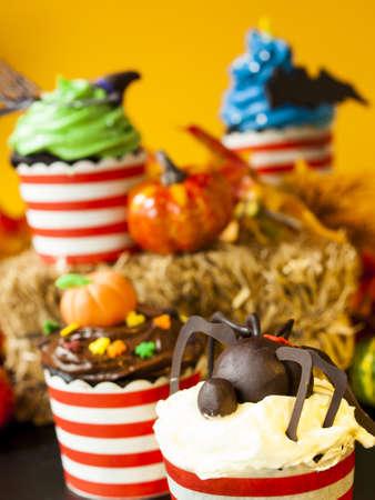 Halloween gourmet cupcakes with holiday decor orange background. photo