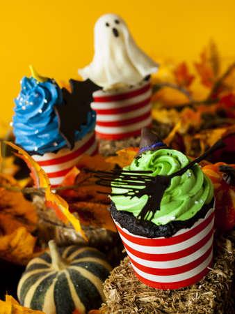 decor: Halloween gourmet cupcakes with holiday decor orange background.