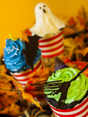 vegetabilis: Halloween gourmet cupcakes with holiday decor orange background.