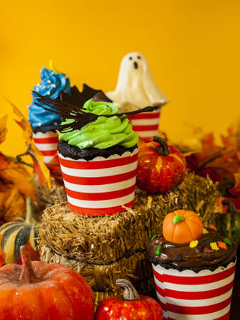 Halloween gourmet cupcakes with holiday decor orange background. photo