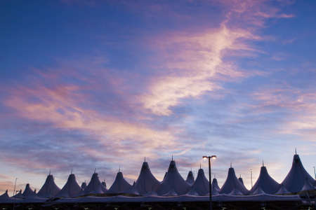 well known: Glowing tents of DIA at sunrise. Denver International Airport well known for peaked roof. Design of roof is reflecting snow-capped mountains.