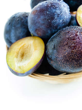 Fresh plums in basket on white background.