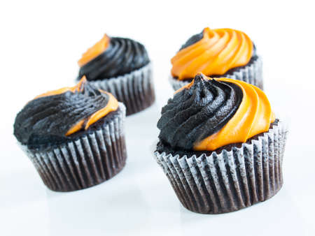 Halloween cupcakes decorated with black and orange swirled icing. Stock Photo