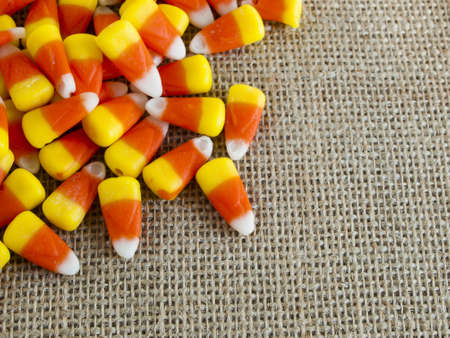 Traditional Halloween candies candy corn on burlap fabric.