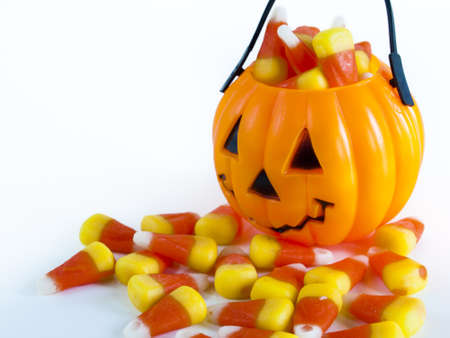candy corn: Halloween treat bag filled with candy corn candies on white background.