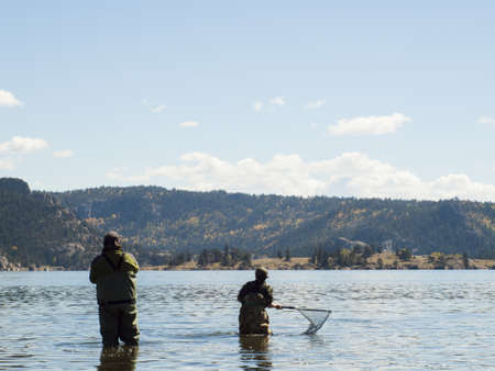 Father and son fishing together on early morning in late Fall. Stock Photo - 15485673
