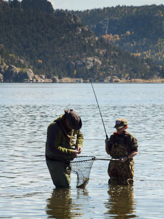 Father and son fishing together on early morning in late Fall. Editorial
