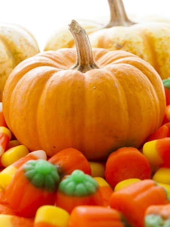 vegetabilis: Small multi-color pumpkins with Halloween candies on white background.